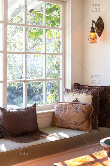 A window seat covered in throw pillows