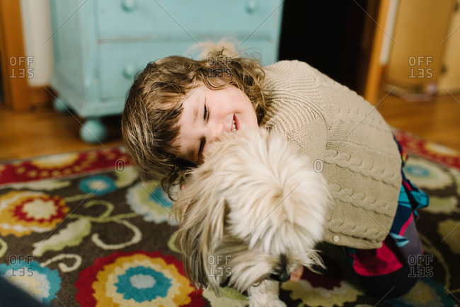 Girl giving dog a hug in home
