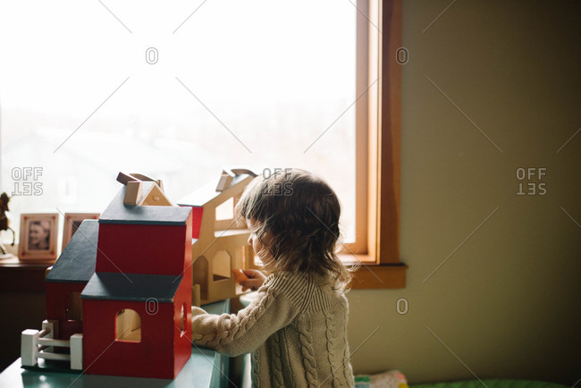 Girl playing with wooden house toy