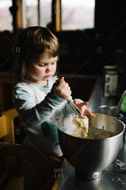 Little girl scooping dough with finger