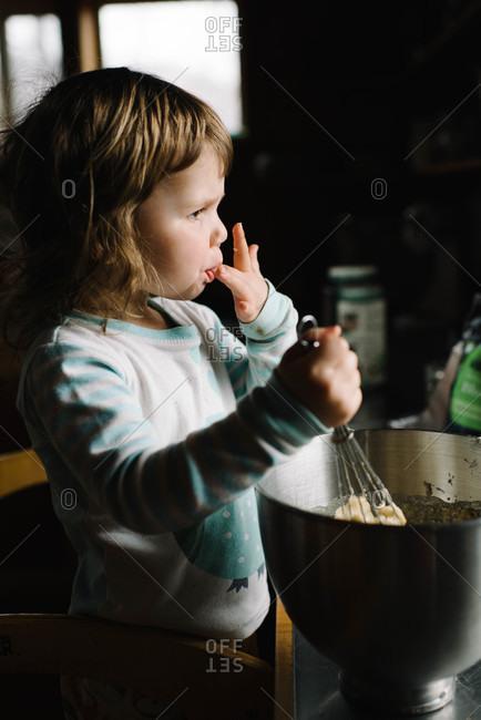 Little girl licking dough off fingers