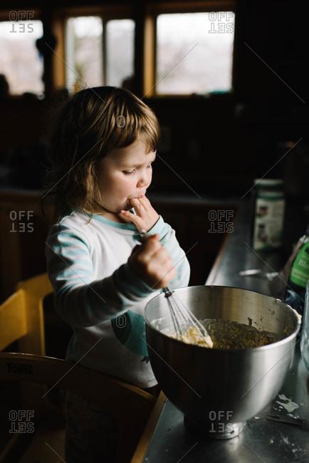 Little girl eating dough with finger