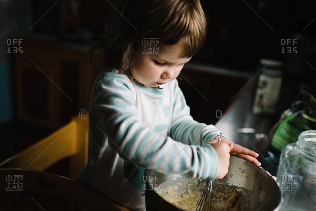Girl stirring bowl of dough