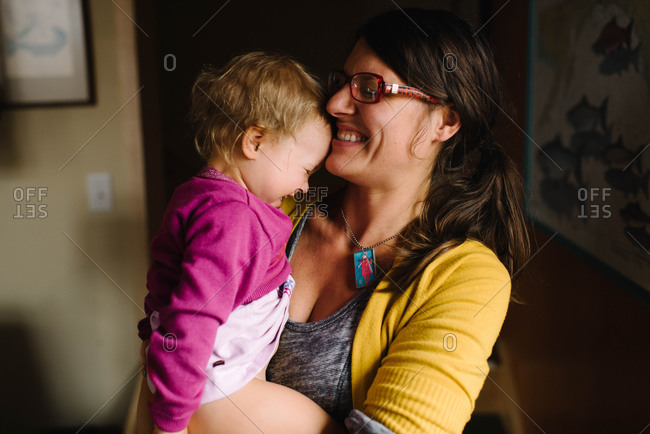 Mom holding giggling young girl