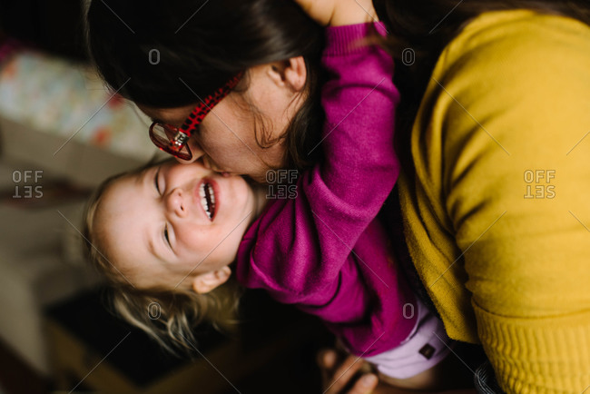 Mom bending over and kissing giggling daughter
