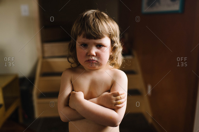 Shirtless pouting girl with arms crossed