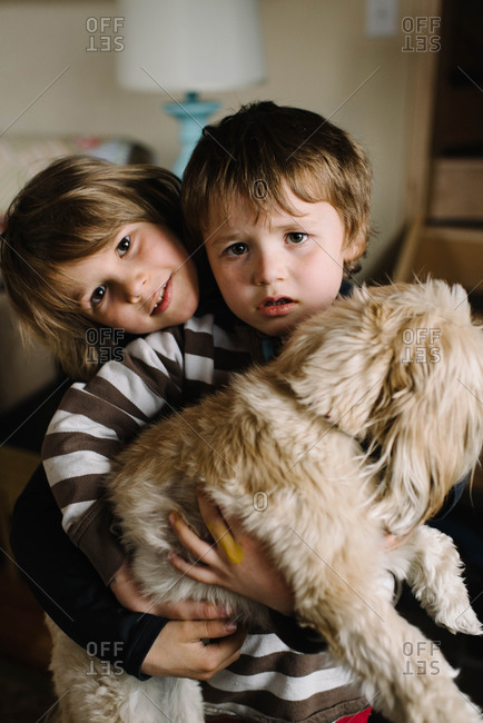 Two young kids holding dog in home