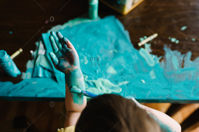 Young girl painting herself and table