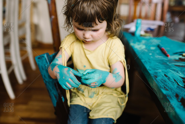 Girl with paint on hands and table