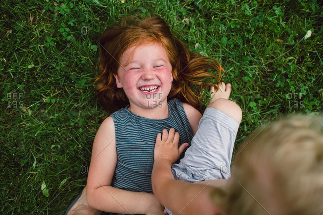 A little boy sits on his giggling sister