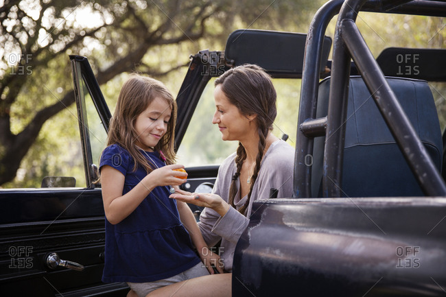 Mom and daughter in open car