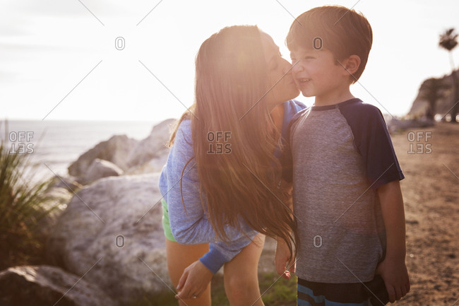 Mom pecking boy's cheek on beach