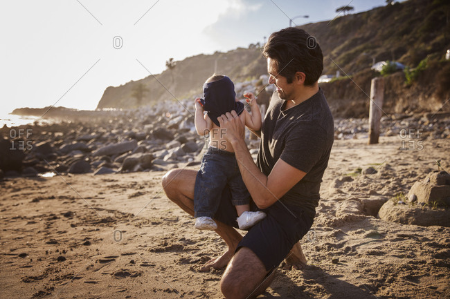 Dad on beach putting shirt on toddler