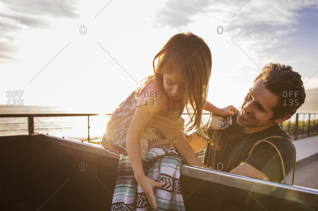 Man helping girl out of back of vehicle