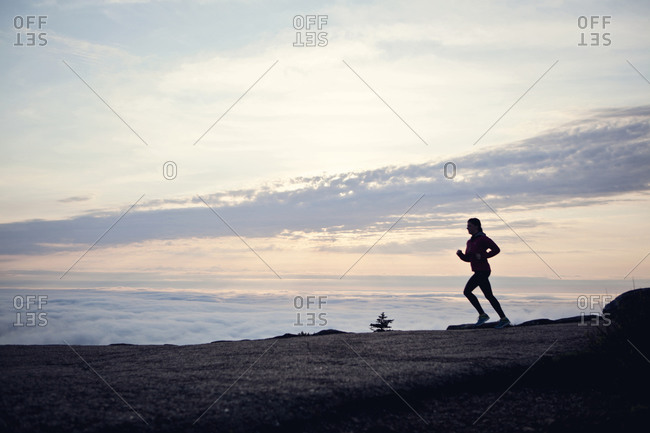 A woman runs at sunrise on Cadillac Mountain, Maine