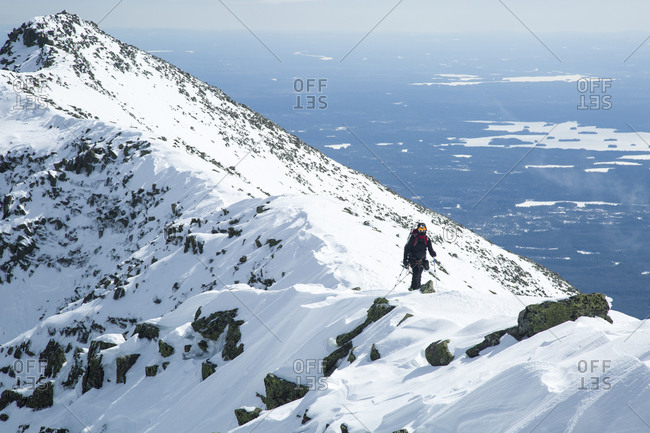 A hiker approaches the summit of Katahdin during a winter hike along the Knife Edge trail in Baxter State Park, Maine