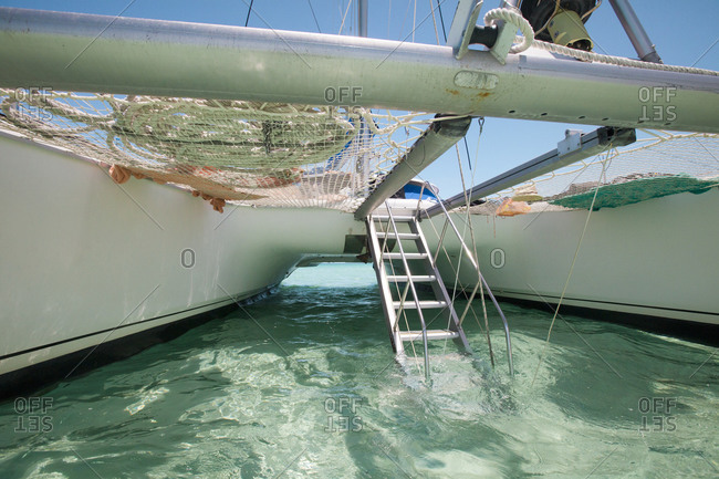 A drop-down aluminum staircase leads up to the deck of a catamaran boat
