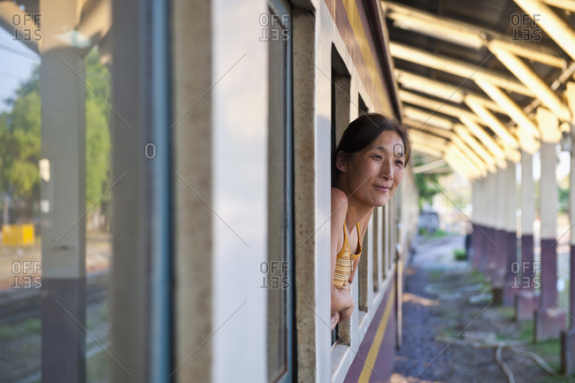 Woman leaning out of train window in Chiang Mai in northern Thailand