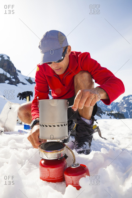 A climber uses a camping stove to make his dinner while camping in the mountains