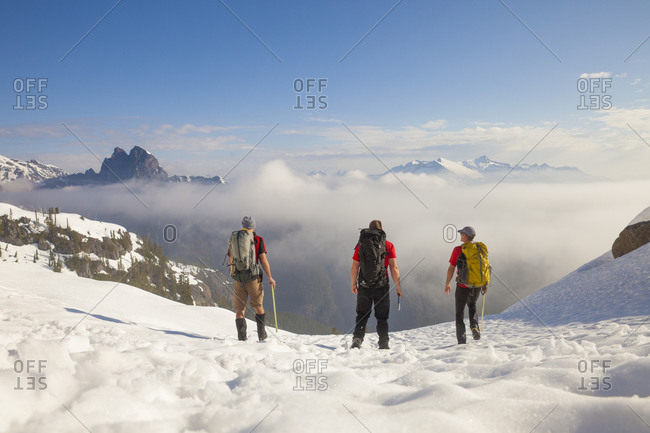 Three backpackers cross a snowfield after a trip into the mountains of British Columbia, Canada