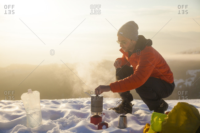 A climber attends to his boiling water on a camping stove while camping in the mountains of British Columbia, Canada