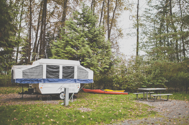 A tent trailer, two kayaks, and a picnic table at a local campground