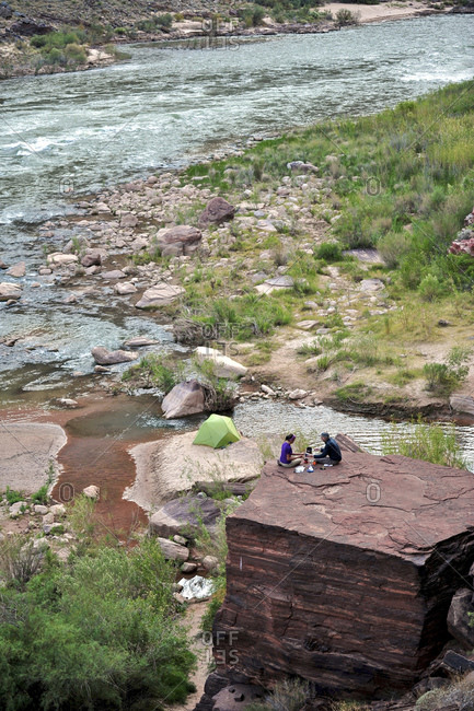 Hikers cook dinner on a cliff-pinched patio above the Colorado River near Deer Creek Falls in the Grand Canyon