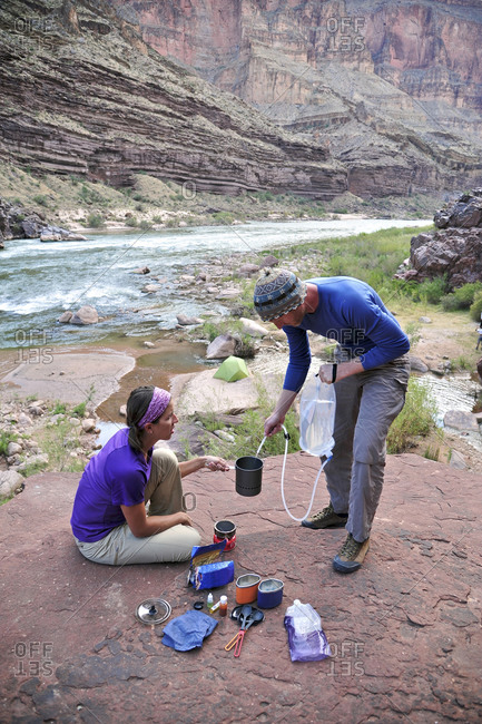 Hikers cook dinner on a cliff-pinched patio above camp and the Colorado River near Deer Creek Falls in the Grand Canyon