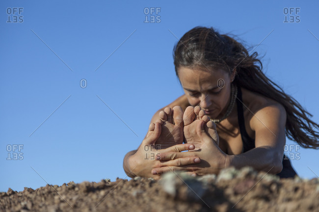 Girl in forward seated bend on the top of a volcano in Fuerteventura, Canary Islands
