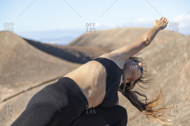 Close up of a girl practicing yoga on the top of a volcano in Fuerteventura, Canary Islands