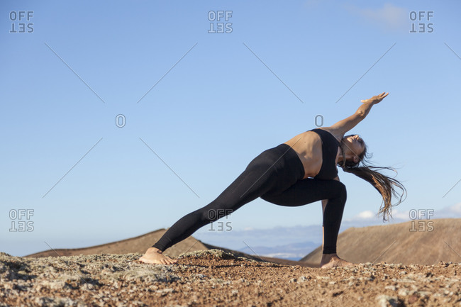 Girl practicing yoga on the top of a volcano in Fuerteventura, Canary Islands