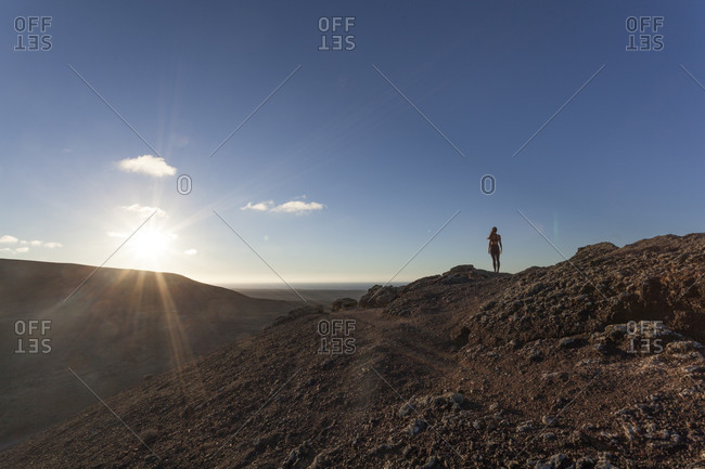 Girl doing yoga on the top of a volcano at sunset in Fuerteventura, Canary Islands