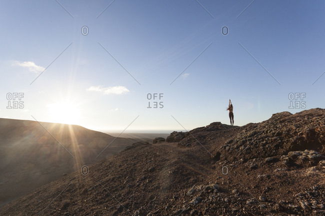 Girl practicing yoga on the top of a volcano at sunset in Fuerteventura, Canary Islands