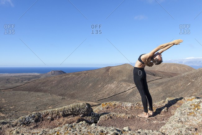 Girl bending backwards on the top of a volcano in Fuerteventura, Canary Islands