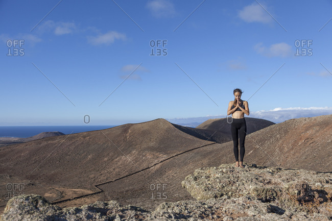 Girl doing yoga on the top of a volcano in Fuerteventura, Canary Islands