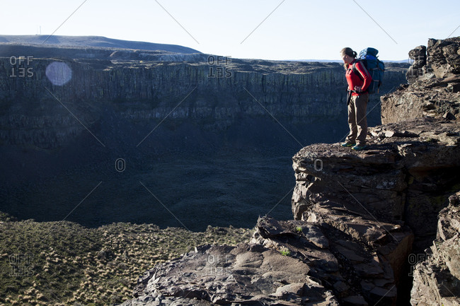 A woman wearing a backpack stands above Frenchman's Coulee, Washington