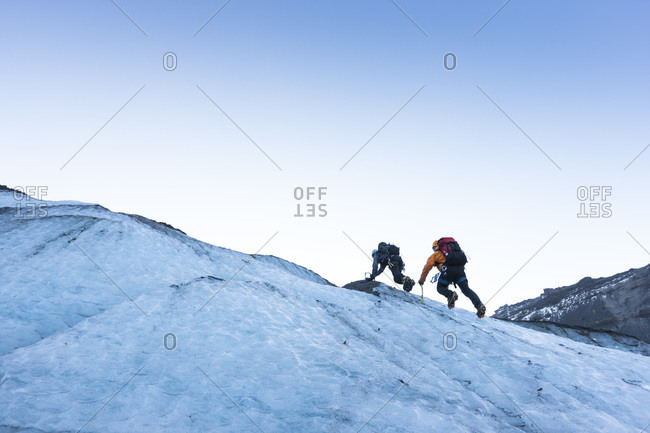 Two climbers ascending a steep glacier ice slope at the glacier Gigjokull South Iceland