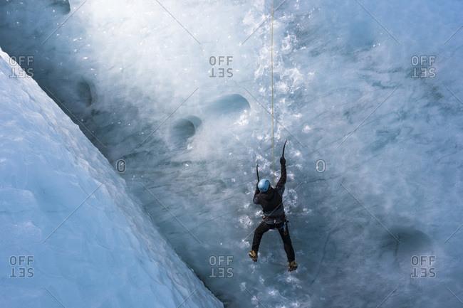 Man climbing a steep glacier ice at the glacier Gigjokull South Iceland