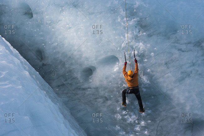 Man climbing a glacier ice at the glacier Gigjokull South Iceland