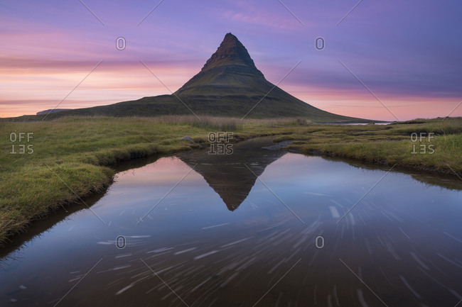A reflection of Kirkjufell mountain on the Snaefellsnes peninsula in western Iceland at sunset