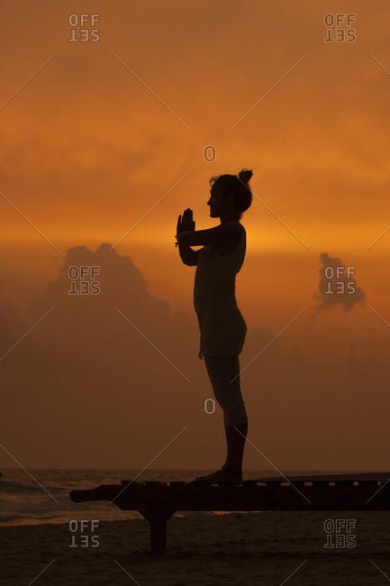 Girl doing yoga at sunset on the beach in Sri Lanka