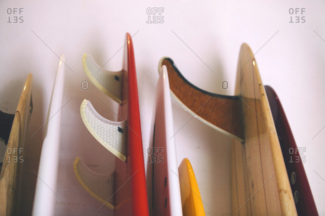 The tails of a series of surfboards rests against the wall in a surfboard shop, Hawaii