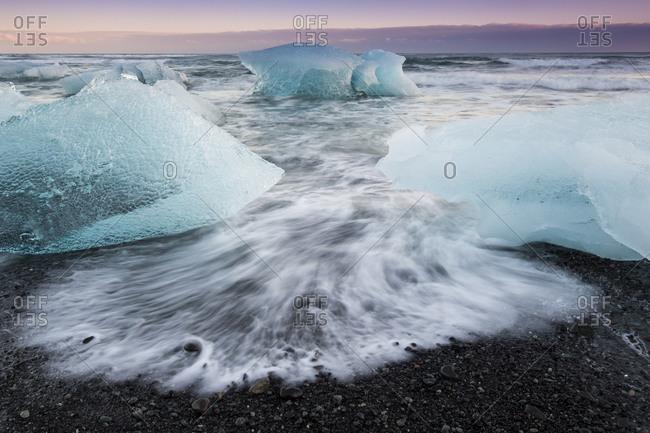 Glacial ice from Breiðamerkurjökull sits on the beach  of the coast at Breiðamerkursandur, Iceland, also known as the Jokulsarlon