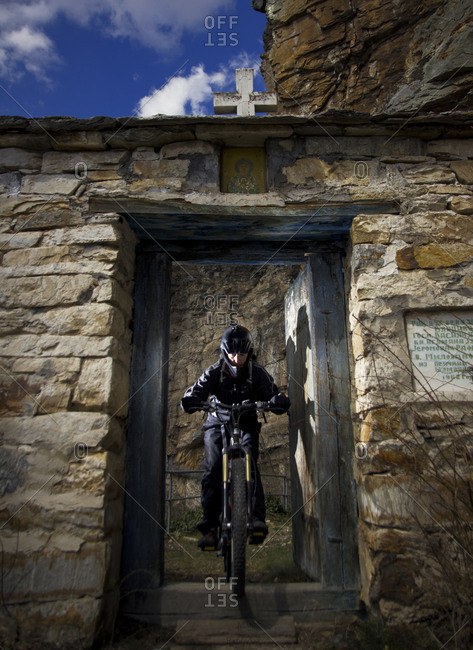 Bicyclist passes through the door of the hermitage of Saint Sava
