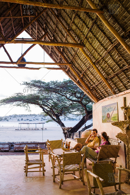 A man and a woman sit in a thatch roof lounge area overlooking an African beach