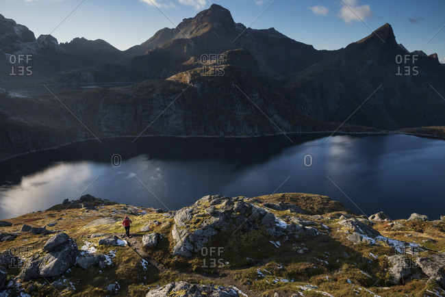 Female hiker on trail near Munkebu Hut with Hermannsdalstind in the background, Moskenesøy, Lofoten Islands, Norway