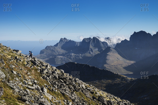 Female hiker ascending a rocky ridge on Branntuva