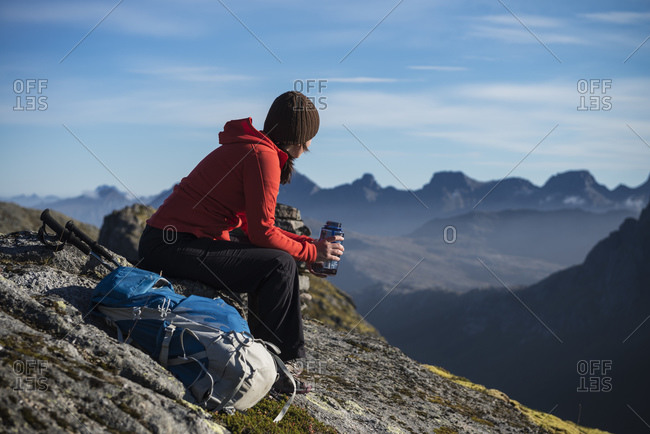 Female hiker takes a break and enjoys mountain views, Moskenesøy, Lofoten Islands, Norway