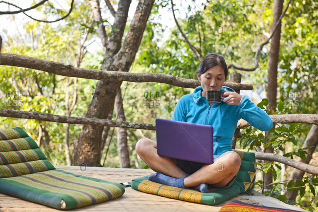 Woman sitting with her laptop on an outdoor terrase at a street cafe in northern Thailand