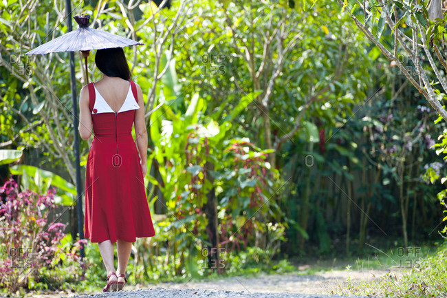 Woman in red dress walking through a Thai garden